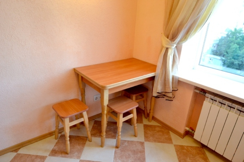 Kitchen with microwave and dining table for three people.
